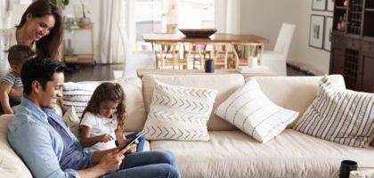 En familj sitter i soffan och kollar på ipad