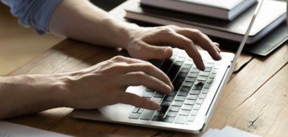 Man skriver på laptop