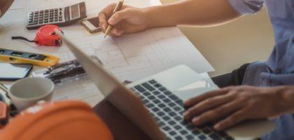 Händer som skriver med penna och på en laptop
